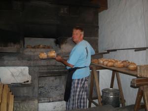 Bakeren med sine nybakte brød fra steinovnen dufter over hele tunet.