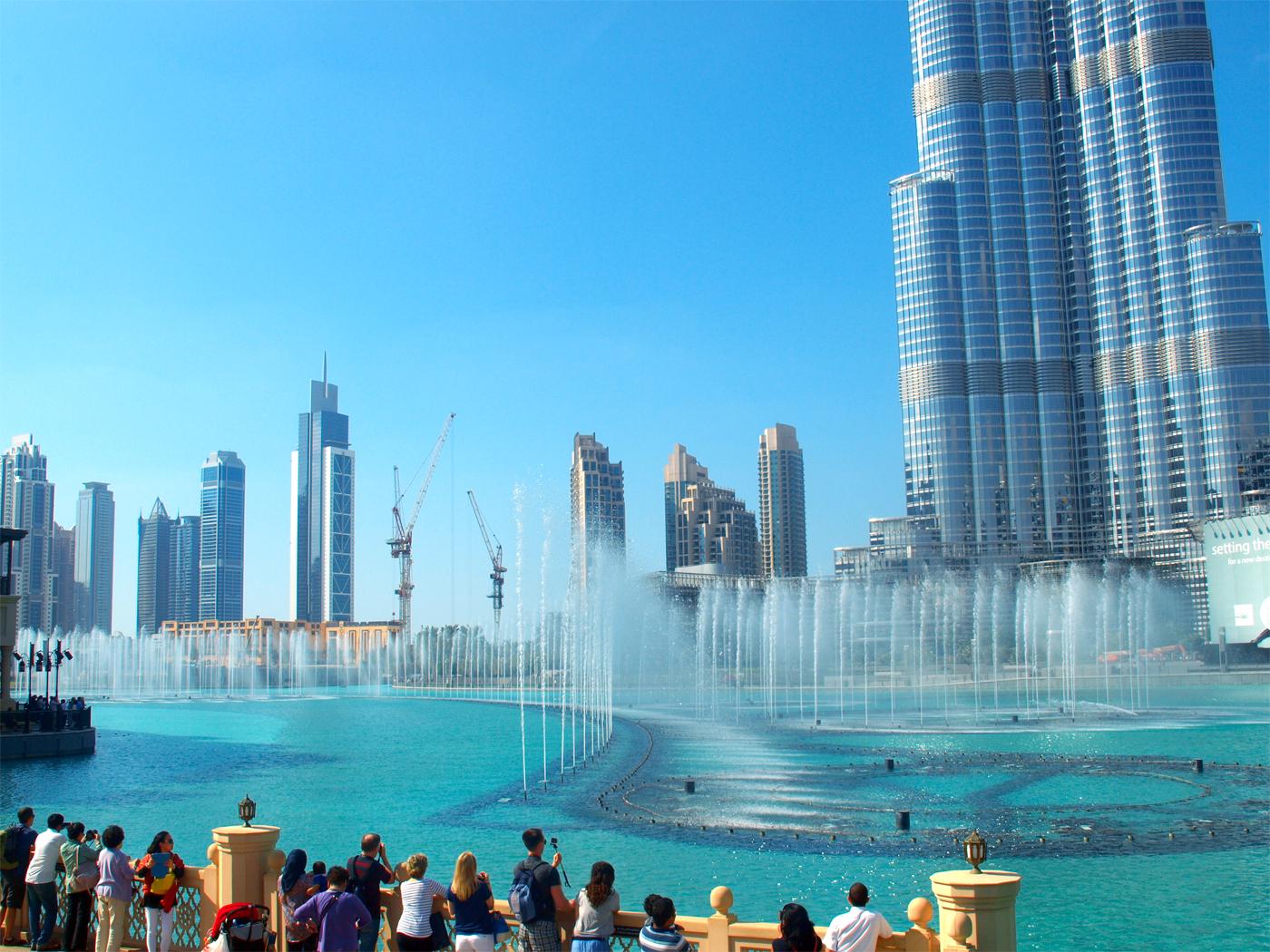 Turister flokker seg rundt oppvisningen av Dubai Fountain som kjører nytt show og musikk hver halvtime fra klokken 13.00. Foto: Yvette-Marie Solem