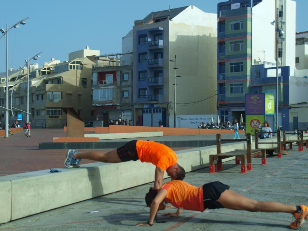 Helt til venstre på strandpromenaden, finnes det utendørs trimapparater. Her viser noen av strandvaktene push-ups. Foto: Yvette-Marie Solem