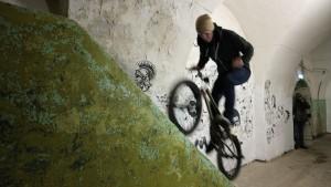 Her er det full fart oppover mosevokste murvegger i oppoverbakke. Her imponerer en biker fra Tallinn til ære for fotografene. Mose og malingsflassete vegger gir en røff ramme til bildet.